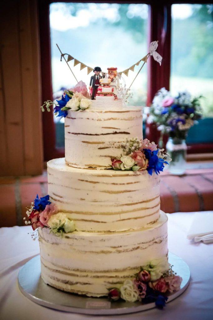 Hell eingestrichener dreistöckiger Naked Cake ist verziert mit pinken und blauen Blumen. Als Cake Topper dient ein Brautpaar aus Lego.